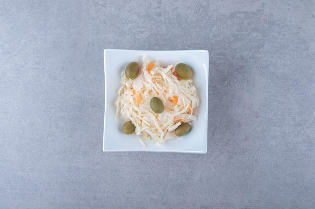 Grandi olive in scatola con i crauti sulla ciotola, sullo sfondo di marmo.