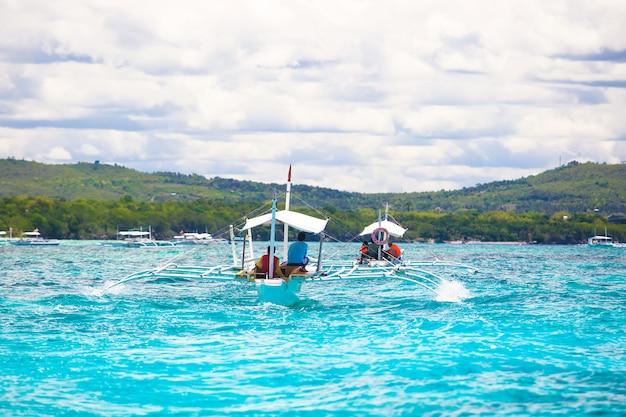 Big catamaran in turquoise open  sea near bohol island