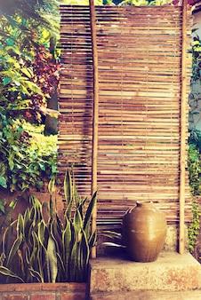 Большая керамическая чаша напротив традиционного азиатского бамбукового забора в окружении экзотических южных растений.
