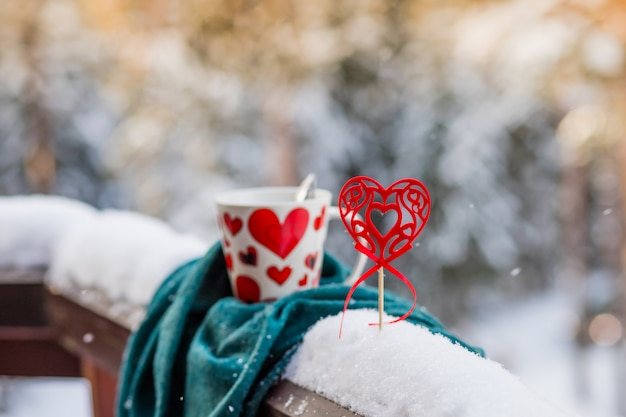 Big ceramic coffee mug on white snow with hearts.cup of black coffee and heart. romantic minimal composition, valentine's day concept. winter coffee. copy space