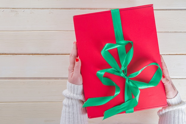 Big christmas gift in woman hands. large red christmas gift box with festive green ribbon, girls hands in pics, top view on wooden background