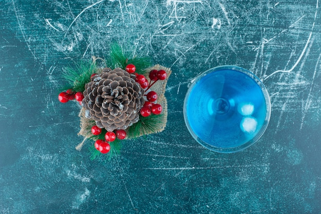 A big christmas pinecone with a glass cup of blue drink.