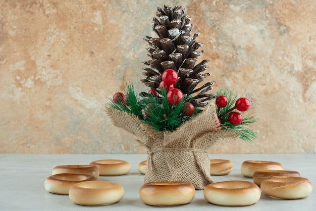 흰색 바탕에 둥근 맛있는 쿠키와 함께 큰 크리스마스 pinecone. 고품질 사진