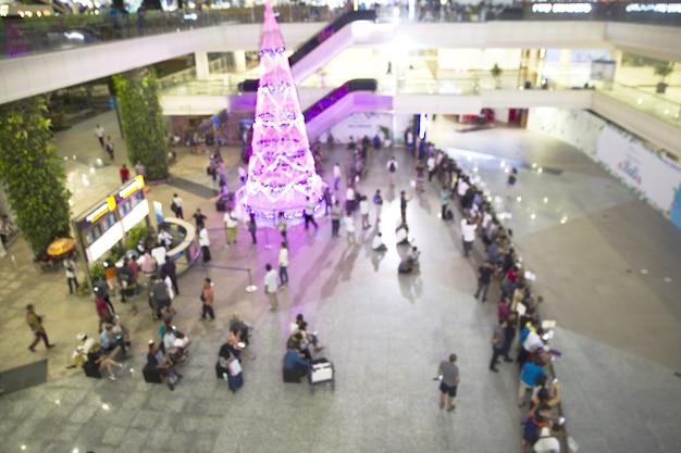 週末に到着または出発するぼやけた人々と空港の大きなクリスマスツリー