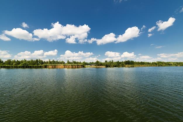 Большое чистое озеро и белые облака в голубом небе. солнечный день.