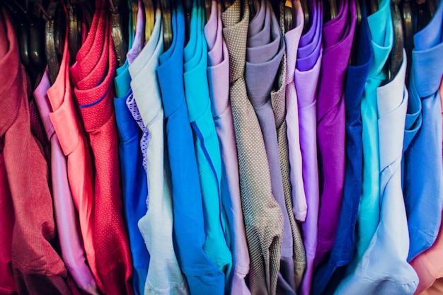 大きな衣料品店、ズボンとtシャツのハンガーが並ぶ多列、さまざまなサイズ