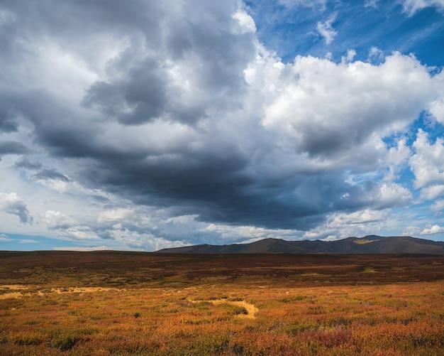 Большое облако над осенней долиной. драматические облака. солнечный свет сквозь темные тяжелые грозовые тучи перед дождем. пасмурно, дождливая непогода. предупреждение о шторме. солнечный свет в грозовом облачном небе.