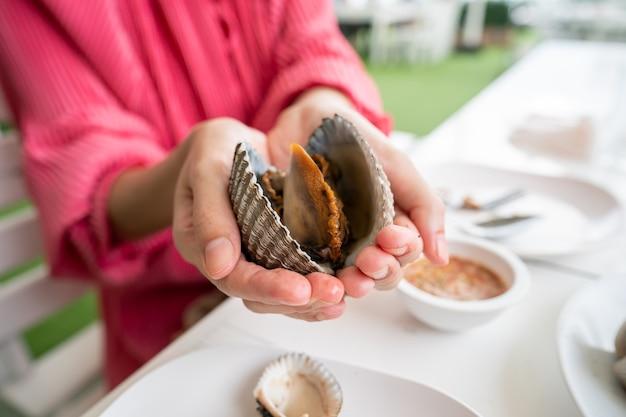 女性の手で大きなザルガイのシーフード、ザルガイまたはホタテの新鮮な貝。