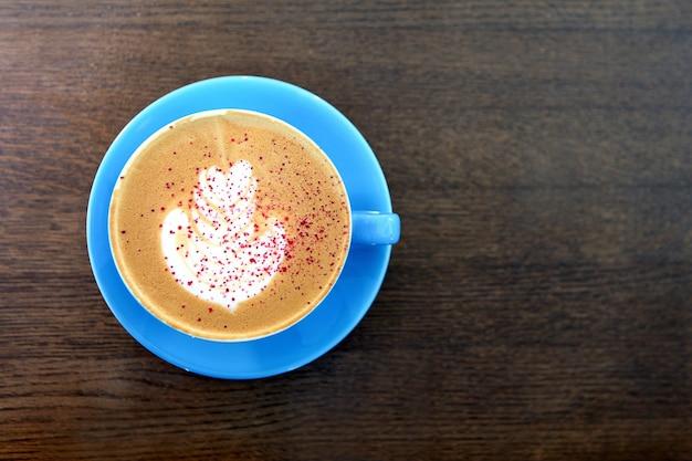 나무 테이블에 우유와 함께 큰 커피 컵. 카푸치노 또는 라떼 음료, 갈색 탁자 위에 놓인 커피 한 잔. 카페오레 한잔. 우유 그림이나 라떼 아트. 파란색 머그에 뜨거운 커피