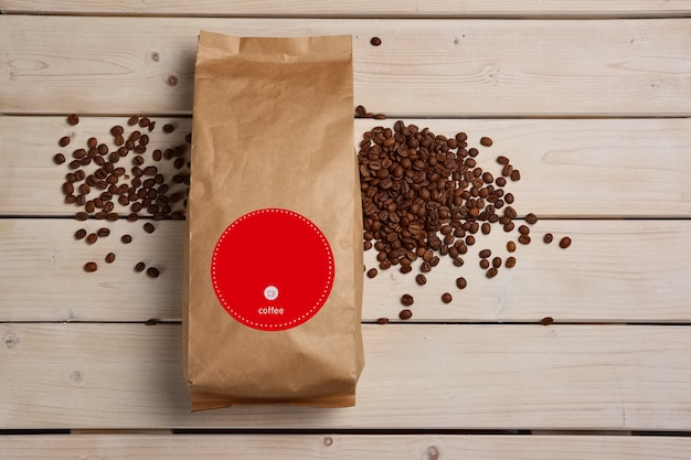 Big coffee paper pack with scattered coffee beans on wooden table. top view.
