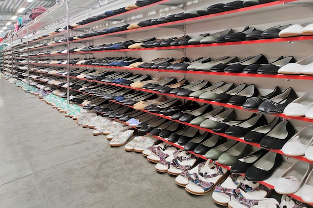 さまざまなスポーツシューズの大きなコレクション。ショーウィンドウには色違いのスポーツシューズがたくさんあります。ユニセックスのメンズレディースシューズ。