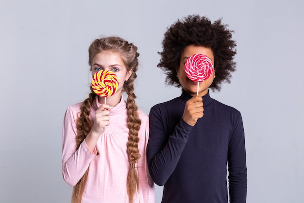 大きなカラフルなキャンディー。大きな青い目と巻き毛の男の子で彼女の顔を覆っている長い光の三つ編みのかわいい女の子