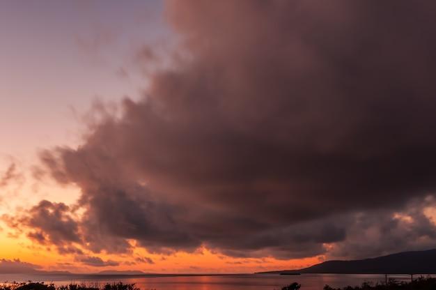 Большое красочное кучево-дождевое облако гуляет над островом исигаки на рассвете