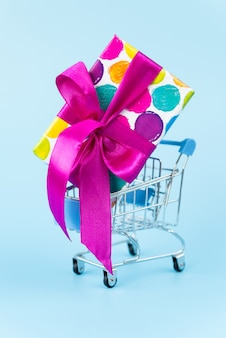 Big colorful gift in shopping cart