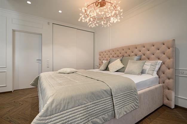 Большая удобная двуспальная кровать в роскошной элегантной классической спальне с ванной.