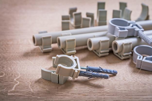 Большой состав полипропиленовые фиксаторы и трубы с зажимами на деревянной доске