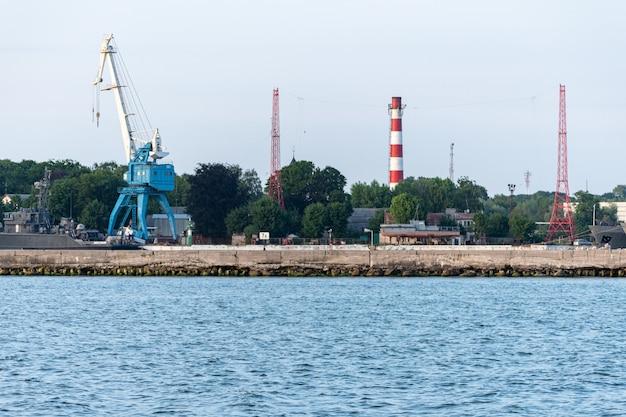Big crane in dockyard. large iron navy ships in shipyard for repair. blue sea harbor