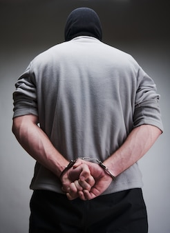 Big criminal locked in handcuffs. terrorist in balaclava