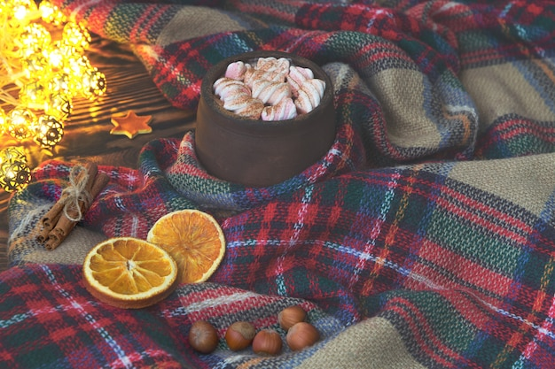 Big cup of hot cocoa with marshmallow, cinnamon and dry orange and warm blanket on an old vintage wooden and christmas light. cozy christmas or autumn arrangement.