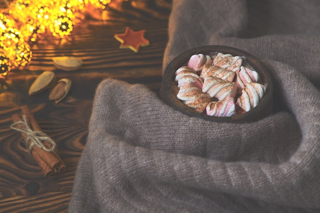 Big cup of hot cocoa with marshmallow, cinnamon and nurs and warm blanket on an old vintage wooden and christmas light. cozy christmas or autumn arrangement.