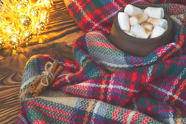 Big cup of hot cocoa with marshmallow, cinnamon and warm blanket on an old vintage wooden and christmas light. cozy christmas or autumn arrangement.