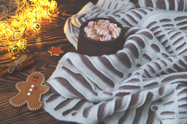 Big cup of hot cocoa with marshmallow, gingerbread, cinnamon and warm blanket on an old vintage wooden and christmas light. cozy christmas or autumn arrangement.