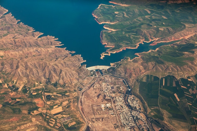 Big dam is a concrete arch-gravity dam on the river in kazakhstan. view of the dam from the airplane window