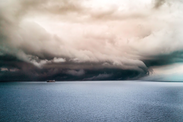 Big dark clouds covering the pure ocean with a ship sailing in it