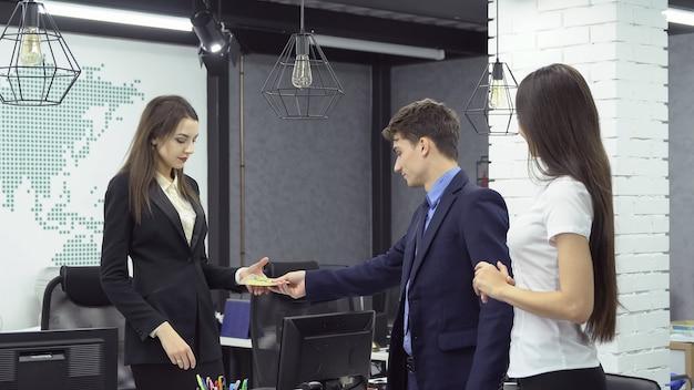 大したこと。フォーマルな服を着た若い男性実業家が若い女性に紙幣の束を与える-オフィスで働いている間、彼のアシスタントの隣にある大企業のボス