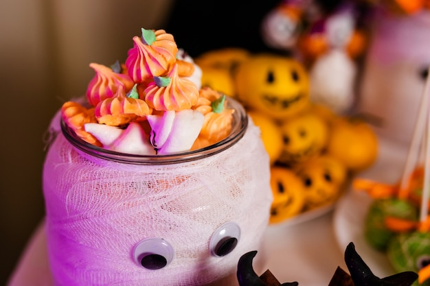 Big decorated jar with pumpkin marshmallows on the candy bar for the celebration of halloween
