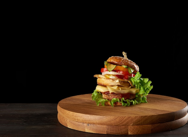 Big delicious burger with meat cutlet, cheese, fried egg, tomatoes, cucumber slices and green lettuce, fast food on a round wooden board, black background, copy space