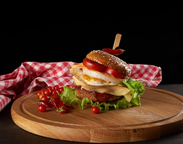 Big delicious burger with meat cutlet, cheese, fried egg, tomatoes, cucumber slices and green lettuce, fast food on a round wooden board, black background