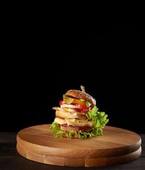 ミートカツ、チーズ、目玉焼き、トマト、キュウリの大きなおいしいハンバーガー