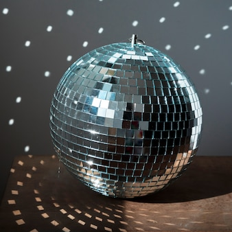 Big disco ball on brown floor with party lights