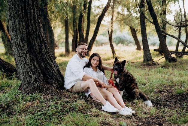 녹색 초원에서 남자와 여자와 산책을위한 큰 개