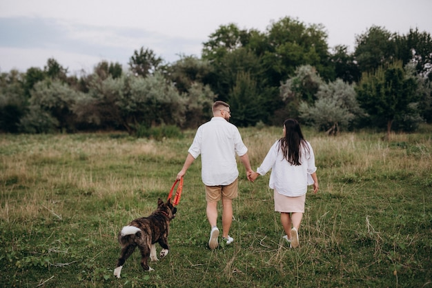 Big dog for a walk with a guy and a girl on the green prairie