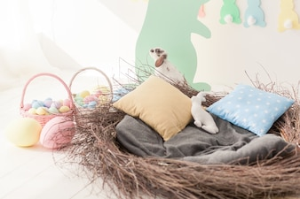Big easter nest with pillows. eggs and rabbit.