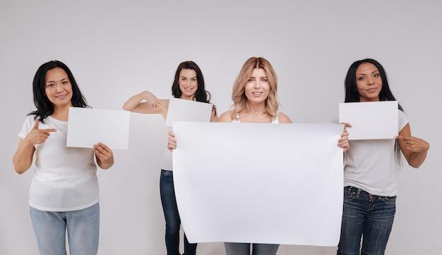 読むのに十分な大きさ。ソーシャルキャンペーンのポーズをとっている間、サイズの異なる白紙を持っている壮大な魅力的な若い女性