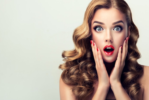 Big expanded eyes widely opened mouth of young surprised and excited womantelling facial expression blonde in the shock