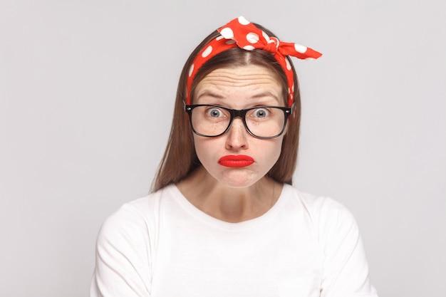 큰 눈은 주근깨, 검은 안경, 붉은 입술, 카메라를 바라보는 머리띠가 있는 흰색 티셔츠를 입은 아름다운 감정적인 젊은 여성의 얼굴에 충격을 받았습니다. 밝은 회색 배경에 격리된 실내 스튜디오 촬영.