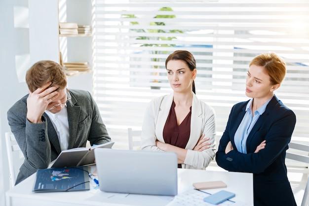 大きな失敗。女性が男性を見つめ、手を組んでいる間、真剣に焦点を当てた3人の同僚が問題について考えています
