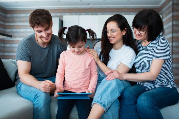 Большая семья дома. все вместе общаемся в онлайн-конференциях на планшете.