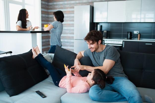 自宅で大家族。ママと娘は互いに通信します。父または兄がソファーで子供と遊ぶ