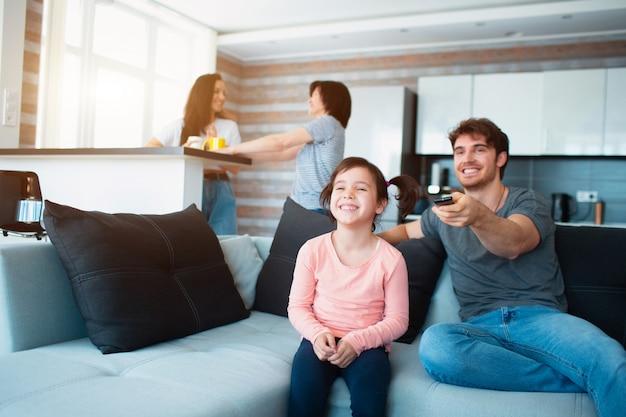 自宅で大家族。ママと娘は互いに通信します。父または兄はテレビを見ます。