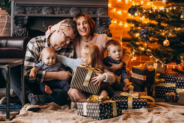 Big family on christmas eve with presents by christmas tree