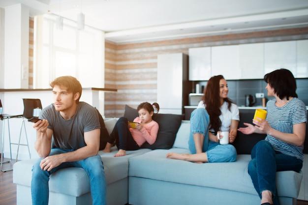 大家族がソファーに座っています。誰もが自分の仕事で忙しい。