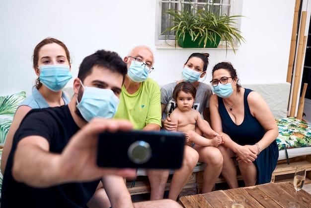 Большая семья делает селфи в хирургических масках