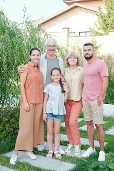 近代的な公園で一緒に立っている5人の大家族、フルレングスのショット