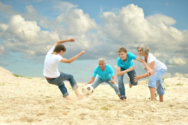 Большая семья играет в футбол на пляже в летний день