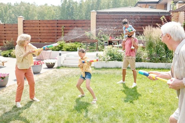 뜨거운 화창한 날씨에 뒤뜰에서 물총을 쏘며 시간을 보내는 대가족